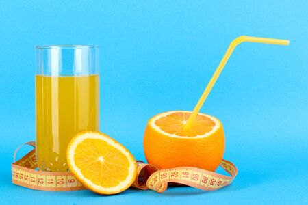 Ripe oranges and juice as symbol of diet on blue background Stock Photo - 15728065