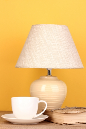 table lamp with cup and book on yellow background photo