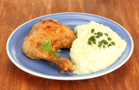 pure patatas: muslo de pollo asado con pur� de patatas en el plato en la mesa de madera de cerca Foto de archivo