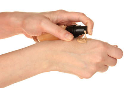 concealer: Woman applying concealer on hand on white background close-up Stock Photo