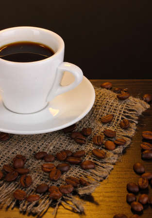 Cup of coffee on wooden table on brown background photo