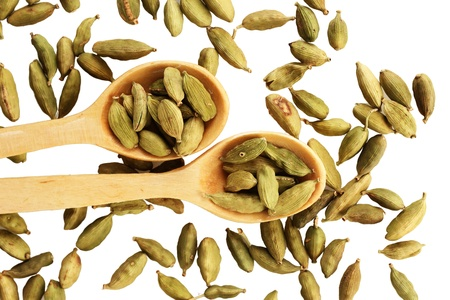 green cardamom in wooden spoons on white background close-up