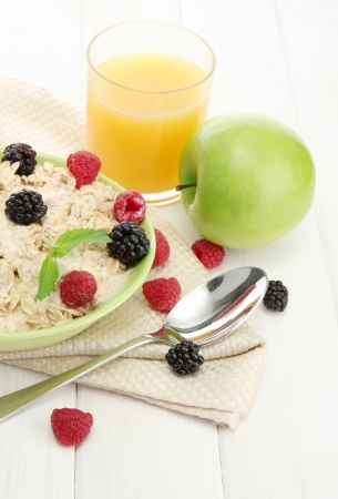 tasty oatmeal with berries and glass of juice, on white wooden table Stock Photo - 15747030