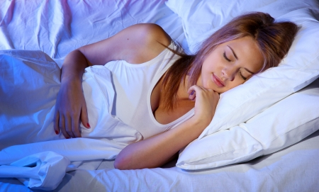 young beautiful woman sleeping on bed in bedroom photo