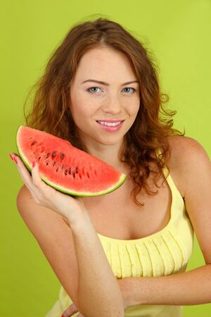 Smiling beautiful girl with watermelon on green background photo