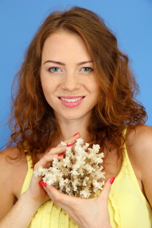 Smiling beautiful girl with coral on blue background photo