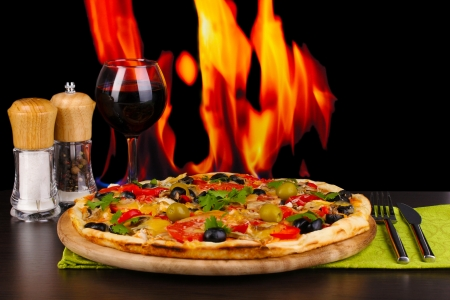 Delicious pizza with glass of red wine and spices on wooden table on fire background photo