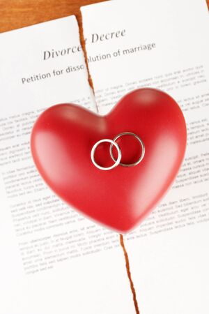 decree: red heart with torn Divorce decree document, on wooden background close-up Stock Photo
