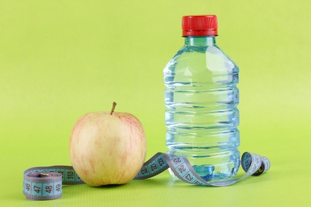 Bottle of water, apple and measuring tape on green background photo