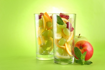 transparent glasses with citrus fruits, on grren background Stock Photo - 15747964