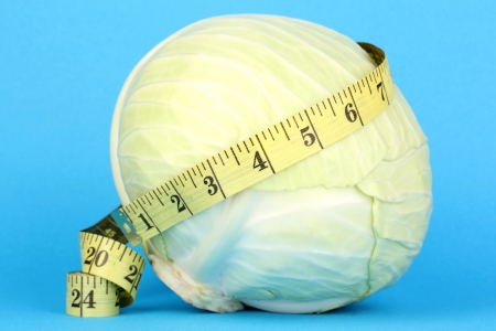 scrawny: cabbage with measuring tape on blue background Stock Photo