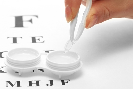 contact lenses in containers and tweezers, , on snellen eye chart background photo