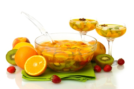 punch in bowl and glasses with fruits, on wooden table, isolated on white photo