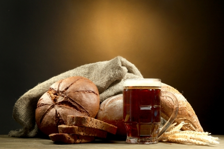 tankard: tankard of kvass and rye breads with ears, on wooden table on brown background