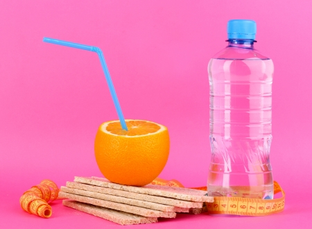 Ripe oranges, loafs and bottle of water as symbol of diet on pink background photo