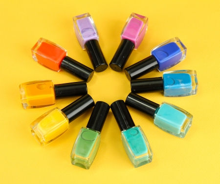 Group of bright nail polishes, on yellow background photo