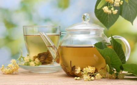 herbal tea: teapot and cup with linden tea  and flowers on wooden table in garden  Stock Photo