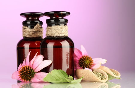 medicine bottles with purple echinacea, on pink background photo