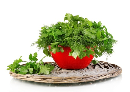 Red pot with parsley and dill on wicker cradle isolated on white photo