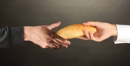 giving hands: helping the homeless, on black background close-up Stock Photo