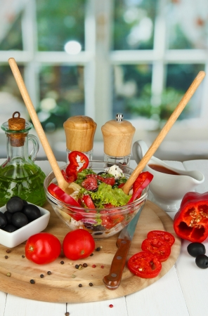 Fresh greek salad in glass bowl surrounded by ingredients for cooking on wooden table on window background Stock Photo - 15782146