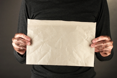 waster: homeless man with cardboard, on black background close-up Stock Photo
