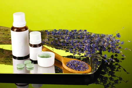 bottles of medicines and herbs on green background. concept of homeopathy photo