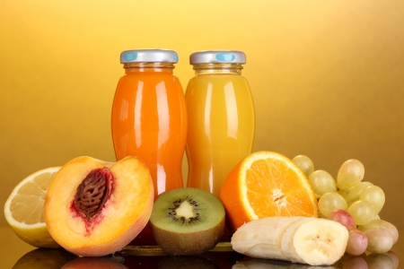 Delicious multifruit juice in a bottle and fruit next to it on yellow background photo