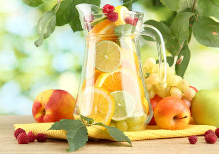 jar with citrus fruits and raspberries, on green background Stock Photo - 15840477
