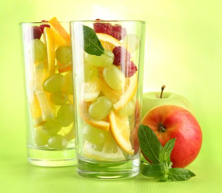 transparent glasses with citrus fruits, on grren background Stock Photo - 15839780