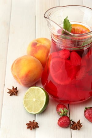 sangria in jar with fruits, on white wooden table photo
