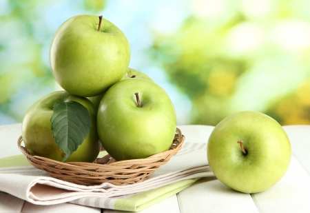 Ripe green apples with leaves in basket, on wooden table, on green background Stock Photo - 15853535