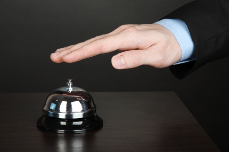 Hand ringing in service bell on wooden table on black background Stock Photo - 15853572