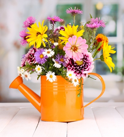 mixed flower bouquet: beautiful bouquet of bright flowers in watering can on wooden table