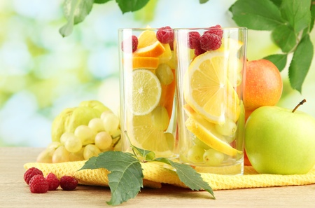 glasses citrus fruits and raspberries, on green background Stock Photo - 15853590