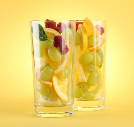 transparent glasses with citrus fruits, on yellow background Stock Photo - 15853245