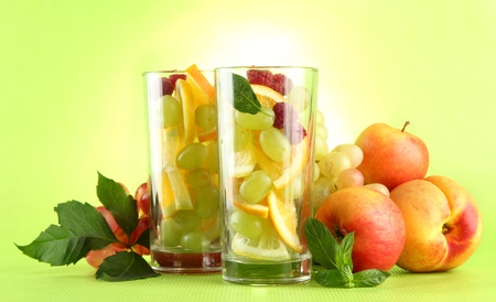 transparent glasses with citrus fruits, on grren background Stock Photo - 15853401