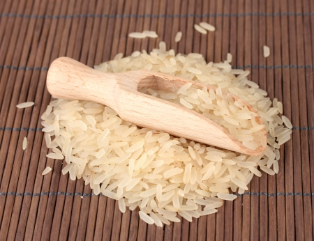 rice  in wooden  scoop on bamboo mat Stock Photo - 15853512