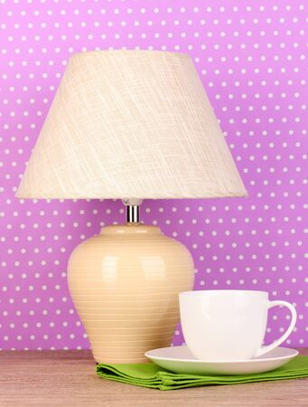 table lamp and cup on purple polka dot background photo