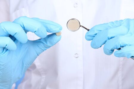 Hands in blue glove holding dental mirror on white background photo