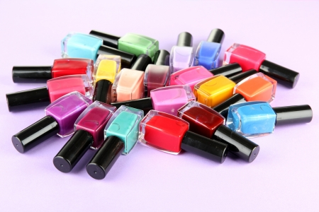 Group of bright nail polishes, on purple background Stock Photo