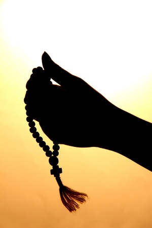 female hands with rosary, on beige background photo