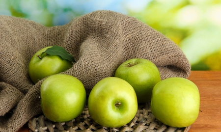 Ripe green apples with leaves on burlap, on wooden table, on green background photo