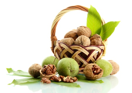 walnuts with green leaves in basket, isolated on white Stock Photo - 15937076