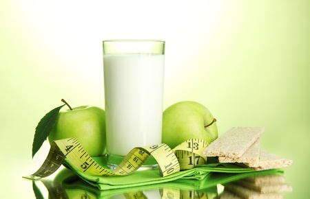Glass of kefir, apples, crispbreads and measuring tape, on green background photo