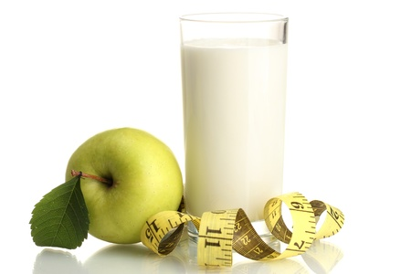 Glass of kefir, green apple and measuring tape isolated on white photo