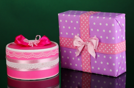 Colorful pink and purple gifts on green background photo