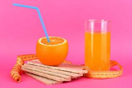 Ripe oranges, loafs and  juice as symbol of diet on pink background Stock Photo - 15937903