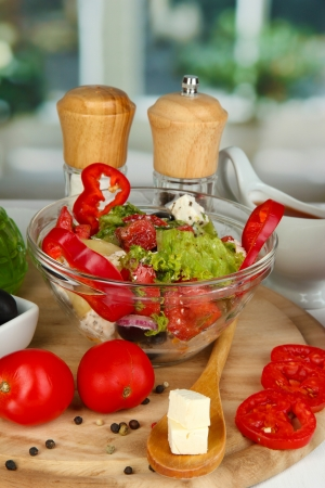 Fresh greek salad in glass bowl surrounded by ingredients for cooking on wooden table on window background Stock Photo - 15938238