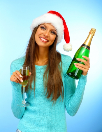 beautiful young woman with bottle and glass of champagne, on blue background photo